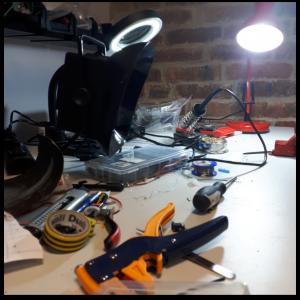 Stół z rozrzuconymi przedmiotami służącymi do pracy w laboratorium elektronicznym