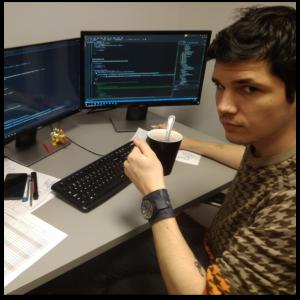 Chłopak siedzący przed monitorami komputera z kubkiem kawy